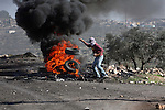 A Palestinian protester burns a tire on the sidelines of a demonstration against the expropriations by Israel in the West Bank village of Kafr Qaddum, near Nablus, on November 30, 2012. Photo by Nedal Eshtayah