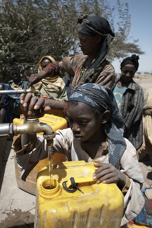 Local woman and children fill water containers at a gravity fed water supply system in Tedecha Guracha, Ethiopia. The source of the water is a natural spring in the highlands 66 km away. Without this supply local people would face a 6 hour round trip to the nearest supply. Villagers pay 5 cents for 25 liters.