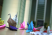 Origami cranes made from paper, a symbol of the Japanese peace movement and longevity, lay on the offerings table at the 'Nagasaki National Peace Memorial Hall for the Atomic Bomb Victims'.  On August 9th the name of RAF Corporal Ronald F. Shaw, killed in Nagasaki on 9th August 1945 in the atomic blast, will offically be dedicated and added to the list of victims.  Shaw was a prisoner of war in the city at the time. Nagasaki, Japan. 08.08.05