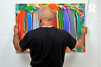 Painter hanging frames on wall (Licence this image exclusively with Getty: http://www.gettyimages.com/detail/105765532 )