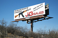 USA. Arizona state. Outside Prescott on the highway. A giant billboard with an AK 47 for sale at the gun shop J&G Sales. The J&G Sales gun shop sells all types of firearms, ammunition and accessories to the public at wholesale prices. The web site offers easy online ordering shipped direct to its customers. The AK-47 (also known as the Kalashnikov, AK, or Kalash) is a selective-fire automatic or semi-automatic gas-operated 7.62×39mm assault rifle, developed in the Soviet Union by Mikhail Kalashnikov. A firearm is a portable gun, being a barreled weapon that launches one or more projectiles often driven by the action of an explosive force. Most modern firearms have rifled barrels to impart spin to the projectile for improved flight stability. The word firearms usually is used in a sense restricted to small arms (weapons that can be carried by a single person). The right to keep and bear arms is a fundamental right protected in the United States by the Second Amendment of the Bill of Rights in the Constitution of the United States of America and in the state constitutions of Arizona and 43 other states. 27.01.16 © 2016 Didier Ruef