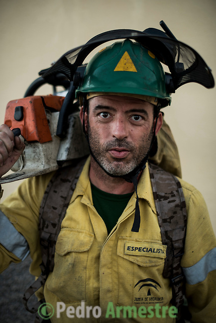Alvaro Joaquin Carballido sanchez. Chainsaw. The firefighter from the BRICA Málaga 703, the Andalusian Service firefighting (INFOCA),  posses after a wildfire in Los Barrios near Cadiz on July 25, 2015. © Pedro ARMESTRE