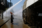 Santiago, Chile<br /> October 1988<br /> <br /> An anti-Pinochet protester defies a government water-cannon prior to the plebiscite.<br /> <br /> In October 1988, General Augusto Pinochet ordered a plebiscite vote asking Chilean citizens whether he should continue in office. It produced a decisive &quot;no&quot; vote and the following year he lost the first presidential election in 19 years. However, under a constitution crafted by his advisors, he remained as army commander until 1998. <br /> <br /> Pinochet continued to wield enormous power until his arrest in London on human rights charges in October 1998.