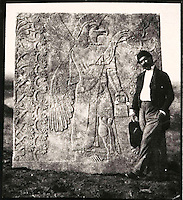 EXCLUSIVE (b/w photo) Victor Place (1818 - 1875) in front of a monumental relief depicting a Eagle-headed winged figure, Nimrud, Iraq, Middle East. Lost at Shatt al-Arab in 1855. (bucket used for magically sprinkling the tree to ensure the fertility of the land)..Additional info :..Victor Place - Génie Ailé à tête d'Aigle. Nimroud N.A. 46.1. Perdu Chatt el Arab 1855. Cliché V. Place. A comparer N° 5 Musée du Louvre.