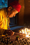 An elderly Tibetan monk lights offering candles in Bodhnath, Nepal.