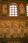 Mosaics in the Basilica of Sant'Apollinare Nuovo in Ravenna, Italy depicting saints and prophets on the top row and a procession of ladies on the bottom row.