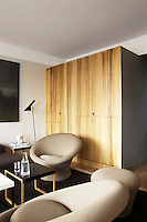 The bookshelf and television are hidden behind the trompe l'oeil cupboard doors painted in imitation wood panels