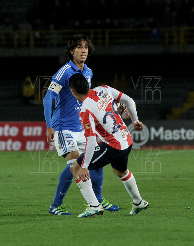 BOGOTA - COLOMBIA -27 - 04 - 2016: Rafael Robayo (Izq.) jugador de Millonarios disputa el balón con Jorge Aguirre (Der.) jugador de Atletico Junior, durante partido de la fecha 15 entre Millonarios y Atletico Junior, de la Liga Aguila I-2016, jugado en el estadio Nemesio Camacho El Campin de la ciudad de Bogota.   / Rafael Robayo (L) player of Millonarios vies for the ball with Jorge Aguirre (R) player of Atletico Junior, during a match between Millonarios and Atletico Junior, for the 15 date of the Liga Aguila I-2016 at the Nemesio Camacho El Campin Stadium in Bogota city, Photo: VizzorImage / Luis Ramirez / Staff.