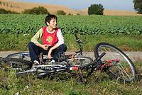 Boy resting after biking through the countryside near the village of Ruy, Isere, France.