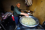 A man cooks in his small restaurant in the Egyptian village of Sakra.