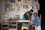 BUKAVU, DEMOCRATIC REPUBLIC OF CONGO - OCTOBER 30: Janette Vumilia, age 30, cleans the table, with her son, after a meal in the living room of her small house on October 30, 2007 Bukavu, DRC. Janette was abducted, held captive and raped by rebels in the DRC conflict. Her hands were amputated before she was finally released. Janette lives with her husband and four children, which is quite unusual, as many men abandon their wives or daughters if they have been raped. The DRC conflict has seen an unprecedented high rate of rape and sexual abuse of women. The culprits are both different rebel groups and government soldiers and very few are punished. About 27,000 sexual assaults were reported in South Kivu province alone in 2006, according to the United Nations. (Photo by Per-Anders Pettersson)