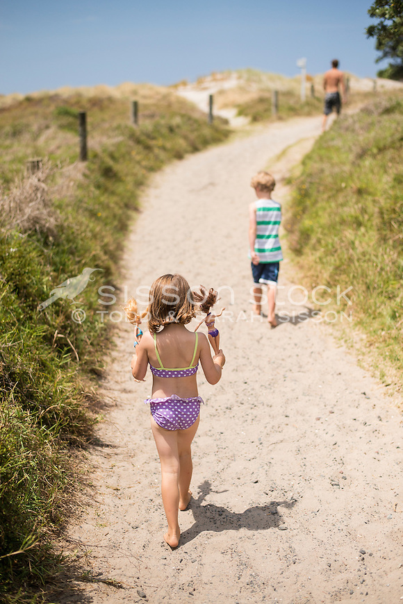 Two children in togs / swimwear walking down a golden sandy path towards the beach and sea on a summers day, Whangarei Heads, Northland, New Zealand - stock photo, canvas, fine art print