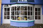 "Portmeirion, in North Wales, is a resort, where no one has ever lived. A self-taught Welsh architect named Sir Clough Williams-Ellis built it out of architectural salvage between the 1920s and 1970s, loosely based on his memories of trips to Portofino. Including a pagoda-shaped Chinoiserie gazebo, some Gothic obelisks, eucalyptus groves, a crenellated castle, a Mediterranean bell tower, a Jacobean town hall, and an Art Deco cylindrical watchtower. He kept improving Portmeirion until his death in 1978, age 94. It faces an estuary where at low tide one can walk across the sands and look out to sea. At high tide, the sea is lapping onto the shores. Every building in the village is either a shop, restaurant, hotel or self-catering accomodation. The village is booked out at high season, with numerous wedding receptions at the weekends. Very popular amongst the English and Welsh holidaymakers. Many who return to the same abode season after season. Hundreds of tourists visit every day, walking around the ornamental gardens, cobblestone paths, and shopping, eating ice-creams, or walking along the woodland and coastal paths, amongst a colourful assortment of hydrangea, rhododendrons, tree ferns and redwoods. The resort boasts two high class hotels, a la carte menus, a swimming pool, a lifesize concrete boat, topiary, pools and wishing wells. The creator describes the resort as ""a home for fallen buildings,"" and its ragged skyline and playful narrow passageways which were meant to provide ""more fun for more people."" It does just that.///Greetings Card Shop at Portmeirion"