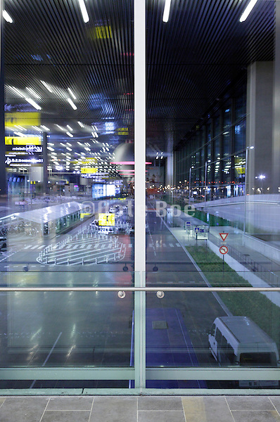 window reflection with airport terminal signage and outdoor parking