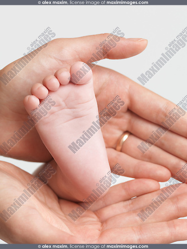 Mother holding her three month old baby son's foot in her hands