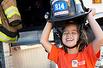 Lia Payne, 5, giggles as she tries on a firefighter hat during National Night Out at Montclaire Elementary School in Los Altos, CA August 6.