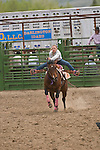 Stacy Wilkinson urges her horse on at the start of her barrel ride during the Jordan Valley Big Loop Rodeo, Ore..