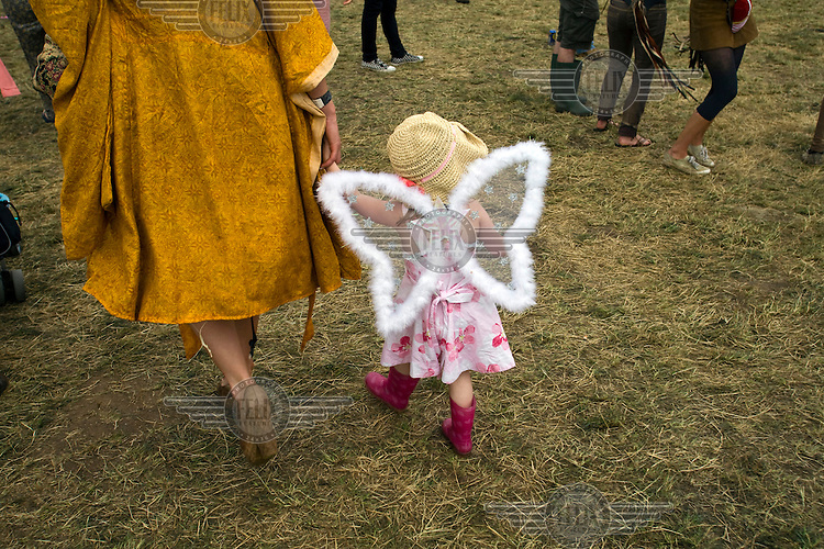 A mother leads her child through a field dressed as an angel at the Standon Calling Festival in Hertfordshire, UK..Standon Calling is a small independent festival set among the hills in Herfordshire that showcases World Music, Indie Music and Dance Music. It is one of the new, small and quirky boutique festivals which have become popular in the UK...
