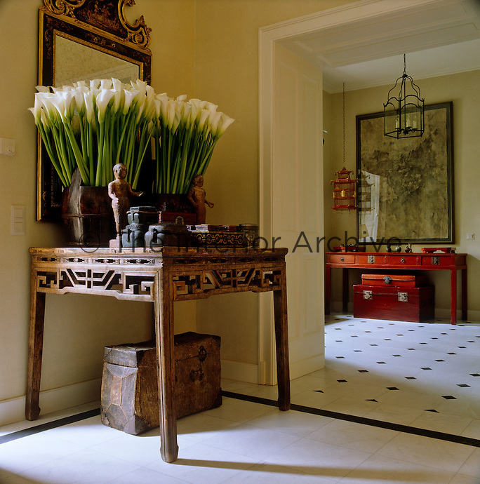 In the hall, a large arrangement of Arum lilies stands on the carved antique Chinese table which is filled with a collection of boxes