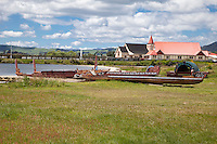 Ohinemutu Village, Lake Rotorua, New Zealand.  Maori canoes under construction.  St. Faith's Anglican Church in Background.