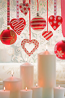 Christmas baubles and home-made hearts hang from coordinated ribbons against the window blind