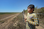 Juan Lovenzo, a 9-year old Wichi indigenous boy, looks through the fence that separates a giant soy bean plantation from Lote 75, an indigenous neighborhood of Embarcacion, Argentina. The Wichi in this area, largely traditional hunters and gatherers, have struggled for decades to recover land that has been systematically stolen from them by cattleraisers and large agricultural plantations.