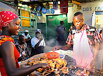 A cook grills chicken at the street market near the ferry in Likoni, Kenya.