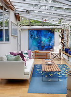 In the conservatory a large comfortable sofa next to a deep blue rug has been heaped with a collection of scatter cushions for maximum relaxation and a large painting in cool greens and ultramarine by Anne Madden takes up an entire end wall