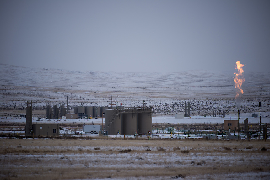 """Natural gas released as a byproduct of oil drilling burns off near petrolium storage tanks outside of Douglas, Wyo., Thursday, November 22, 2013. The state will require pre-drilling testing of groundwater at sites where hydraulic fracturing, also known as """"fracking"""" is used. (Kevin Moloney for the New York Times)"""