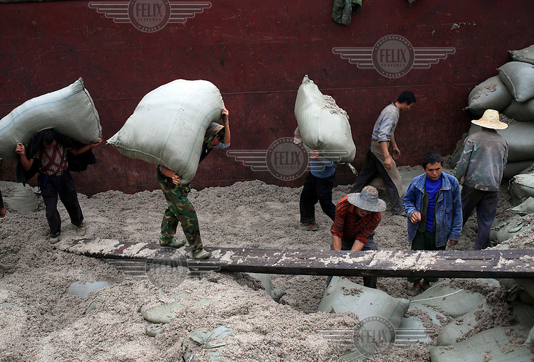Labourers unload sacks of asbestos from a barge in Chongqing.