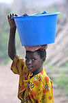 A girl carries water in the Congolese village of Wembo Nyama.