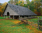 Cantilever style barn and old farm implements and fence, Pioneer Homestead at the Oconoluftee Visitor Center, Great Smoky Mountains National Park, North Carolina, USA.