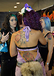 Garden City, New York, USA. 14th September 2014. LEI LANI is the newly crowned Ink Angel, seen from the back in purple with tattoos of flowers, at the United Ink Flight 914 tattoo convention at the Cradle of Aviation museum of Long Island.