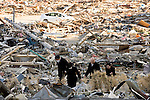 Mourners walk through the rubble of their former homes in Rikuzentakata, Iwate Prefecture, Japan on 06 April, 2011. .Photographer: Robert Gilhooly