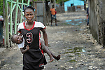 A girl carries her sister along a street in Batey Bombita, a community in the southwest of the Dominican Republic whose population is composed of Haitian immigrants and their descendents.