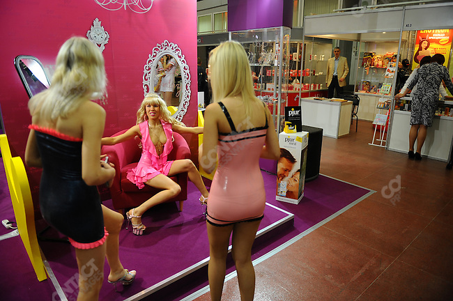 At the X-Show in Moscow, a show with stands selling and promoting businesses involved in the erotic industry, girls handing out flyers stopped for a photo. Moscow, Russia, May 28, 2010