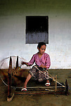 A woman spinning silk the traditional Lao way in Xieng Khuang, Laos.