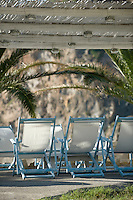 A group of blue wooden deck chairs with white canvas seats on the covered terrace