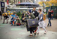 Shoppers leave an H&M store in New York with their Balmain x H&M purchases on Thursday, November 5, 2015. The collection, designed by the young head of Balmain, Olivier Rousteing, was highly anticipated by fashionistas and drew crowds around the world. In New York H&M instituted a wristband system to time when shoppers could arrive to control crowds. (© Richard B. Levine)