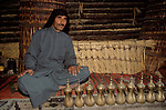 Marsh Arabs. Southern Iraq. Circa 1985. Marsh Arab man in communal village reed constructed building with coffee pots. Haur al Mamar or Haur al-Hamar marsh collectively known now as Hammar marshes Irag 1984
