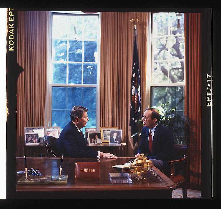White House. .President Ronald Reagan, at his desk in the Oval Office, speaking with republican senator Alfonse D'Amato of New York. Washington, D.C., 1987.