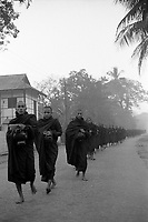 Monks from Kha Khat Wain Kyaung, one of the three largest monasteries in Burma, collect alms in Bago (Pegu) early in the morning.
