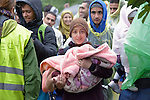 A woman holds a baby in her arms as she approaches the border into Croatia near the Serbian village of Berkasovo. Hundreds of thousands of refugees and migrants from Syria, Iraq and other countries--including many children--have flowed through Serbia in 2015, on their way to western Europe.