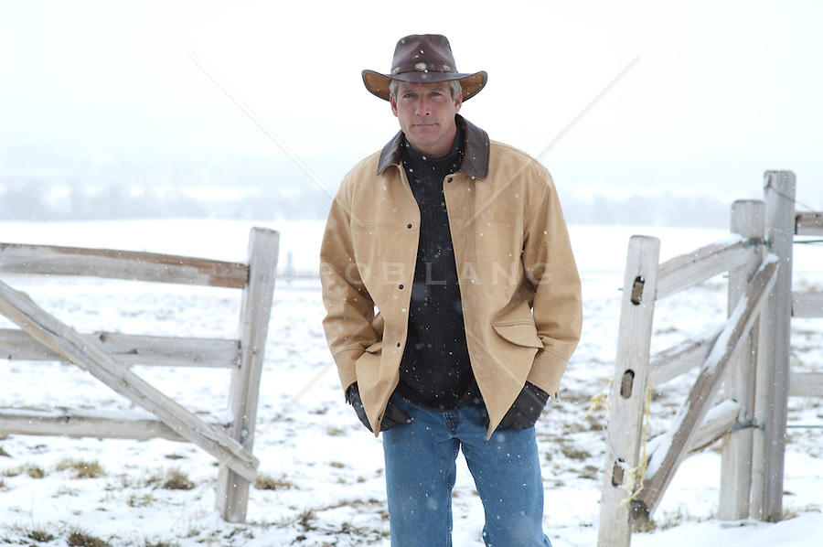 rugged cowboy walking through an open fence in a snow storm