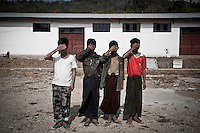 Burmese child soldiers (17 years old) cover their faces to avoid be recognized as they keep under custody by the KIA intelligence inside a detention centre in the stronghold Laiza city. They were forced to become soldiers by the Burmese army, but they escaped from the army when got the chance. They are desertors now without any chance to go back home.