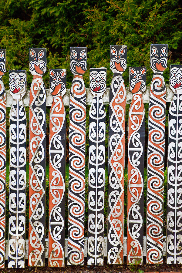 Maori Picket Fence, Government Gardens, Rotorua, north island, New Zealand.  Designs on the pickets depict Maoris sticking out their tongues, a common gesture in traditional Maori war dances (haka) designed to intimidate the enemy.