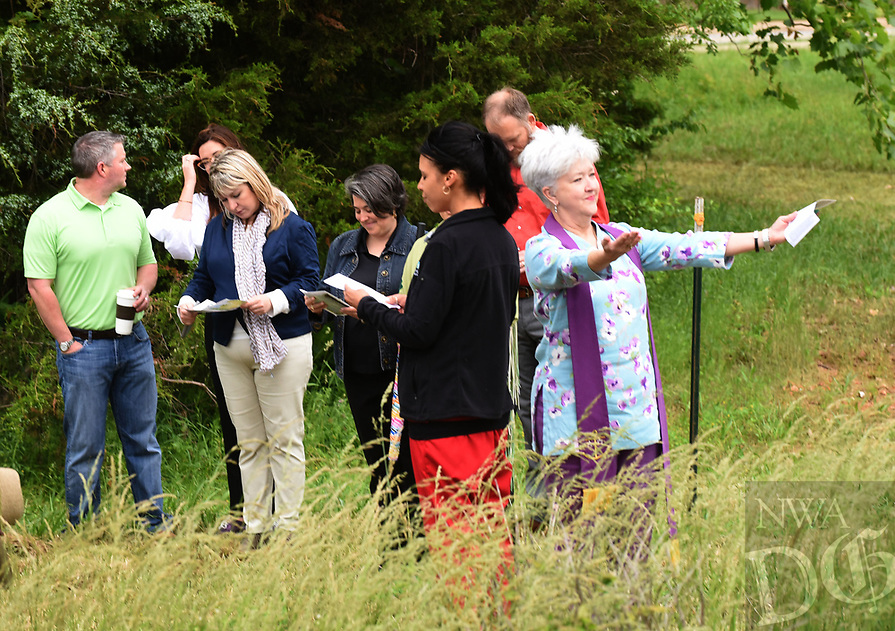 NWA Democrat-Gazette/FLIP PUTTHOFF <br /> GARDEN BLESSING<br /> Rev. Pamela Cicioni, spiritual director at Highlands Oncology Group in Rogers (right), leads a blessing of the land walk Wednesday May 17 2017 at the site of the Healing Gardens of Northwest Arkansas. The garden will be built near the west entrance of Highlands Oncology Group on South 52nd Street. In addition to flowers, plants and trees, the garden will feature a waterfall, reflecting pool, sanctuary and walkways. The garden property is adjacent to the Razorback Greenway and will be open to the public. A fundraising campaign will begin soon to help fund construction, Cicioni said. An estimated completion date has not been set.