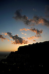 Clouds at dusk behind silhouetted cliffs at Mogan, Gran Canaria, Canary Islands, Spain.