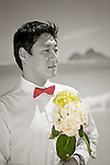 Asian groom waits for his bride with a bouquet of flowers during a stroll on Lanikai beach as they look forward to their life as a married couple following their wedding. Color and BW cutout