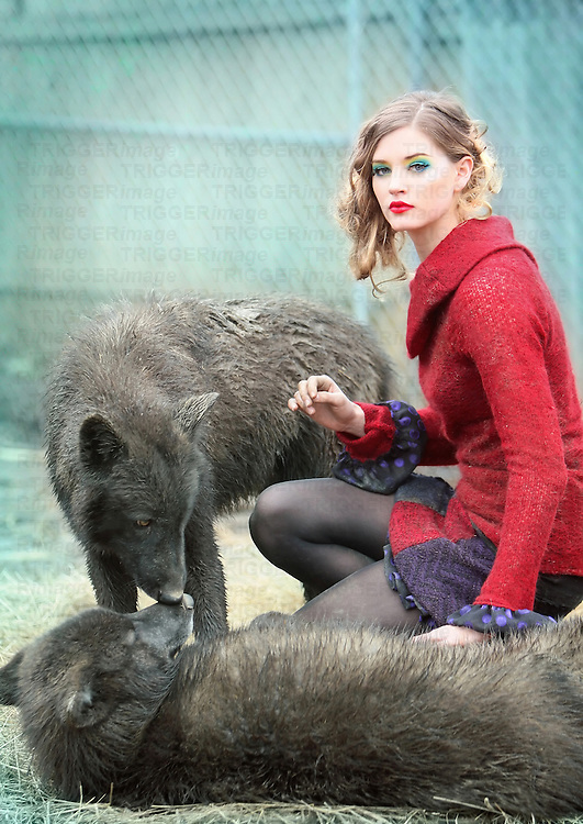 A beautiful woman with vibrant makeup and a bright red sweater kneels down between two kissing wolves